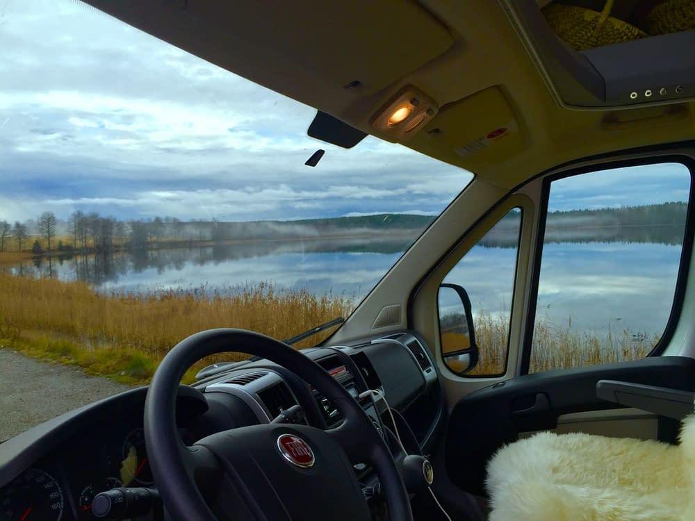 Husbil framruta vy sjö om höst