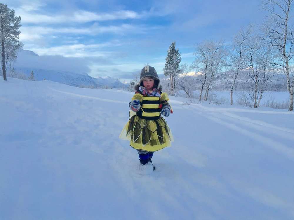 Barn i humledräkt på snö
