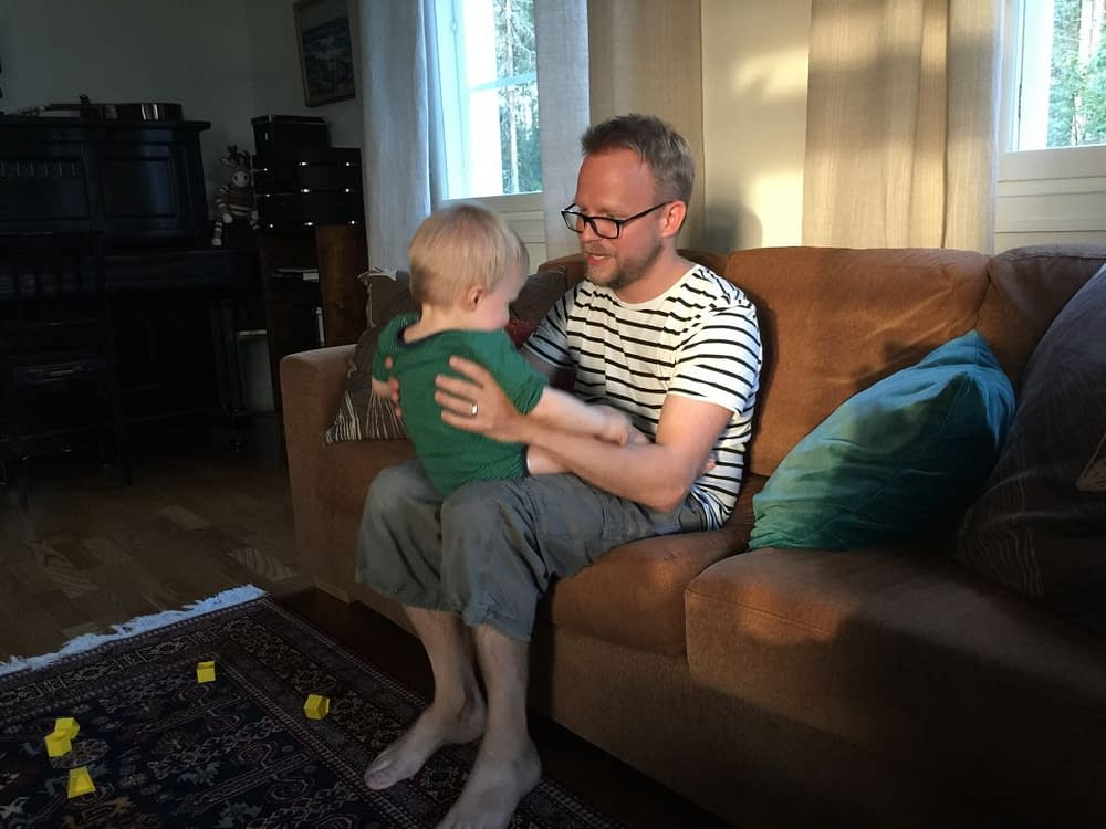 Pappa med liten unge på knät sjungande.