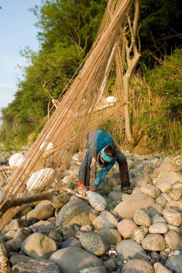Malin Skinnar bygger skulptur med hampa, stockar och stenar på Landart festival Rugen.