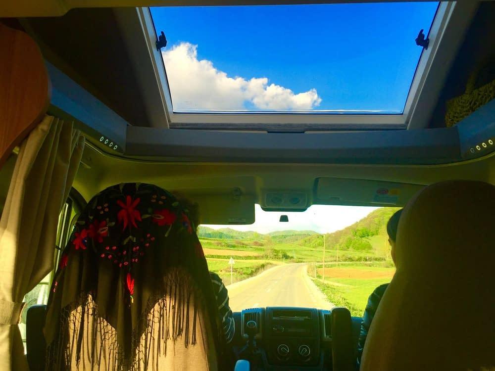 Vyn från baksätet på en husbil med stort takfönster och blå himmel