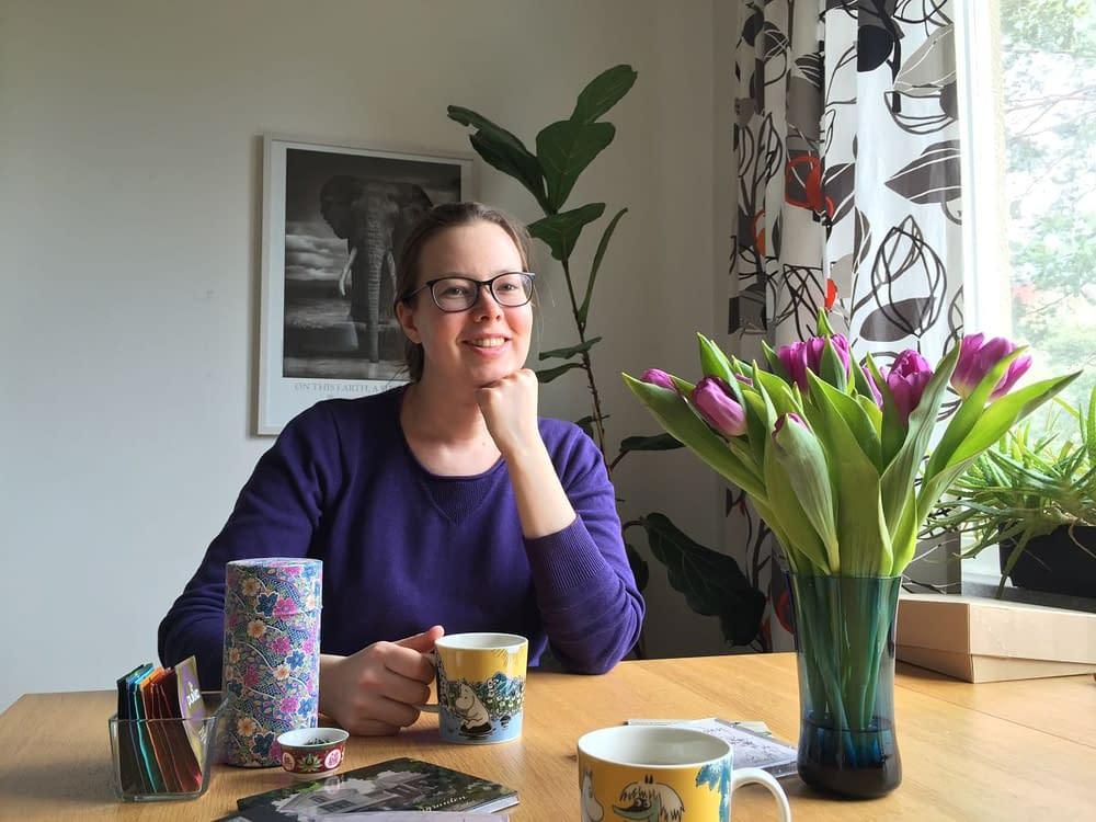 Kvinna framför lila tulpaner i lila tröja